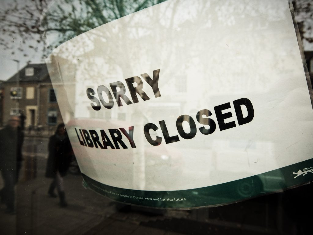 """Sorry Library Closed sign"" with reflection of library and campus in the glass."