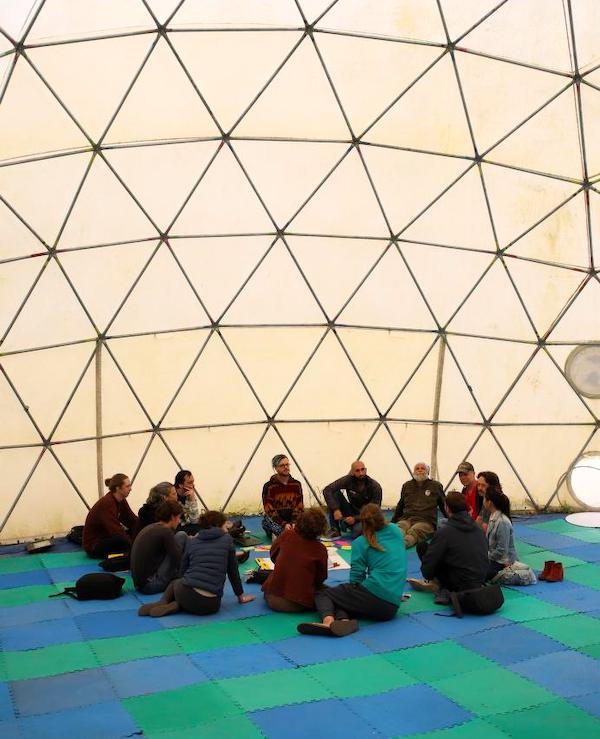 A group discussion inside the Dome of Decentralization at DWeb Camp 2019. A group of people sit inside a white geodesic dome.