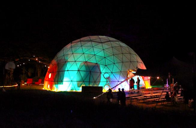 The Dome of Decentralization at night, DWeb Camp 2019. A colorful geodesic dome lit from the inside, silhouettes of people scattered in groups around it.