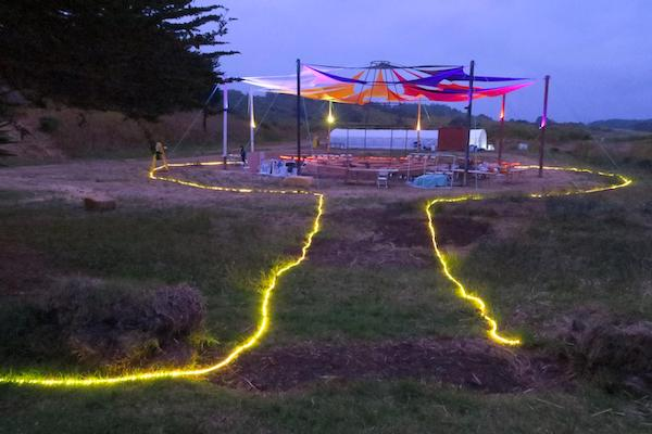 Evening at the Wayback Wheel at the Mushroom Farm, DWeb Camp 2019. Up against a backdrop of a foggy skyline, a colorful shade structure stands ahead with a lit path leading up to it.